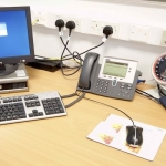 The desk of a GP with a computer, phone, and blood pressure monitor on