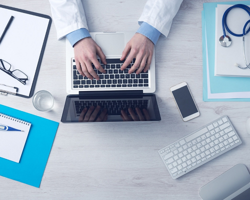 Doctor sat at a desk using a laptop with various paperwork, a stethoscope and a phone.